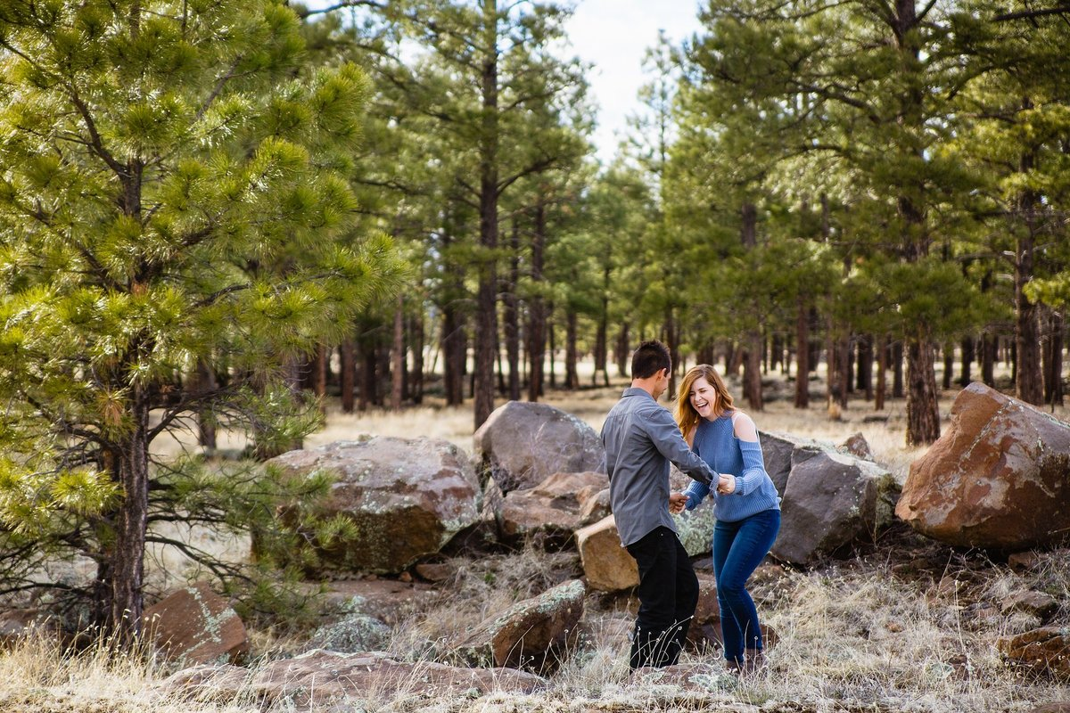 Couple laughing and having fun together during their Buffalo Park engagement session by adventure engagement photographer PMA Photography.