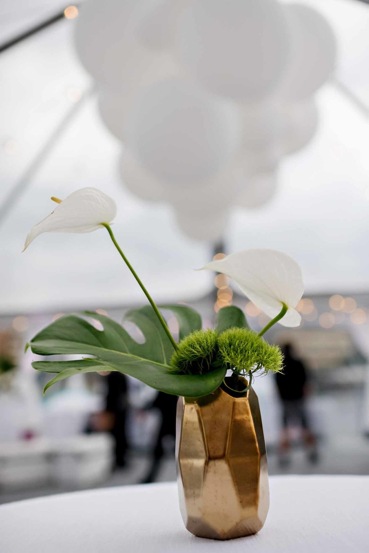 centerpiece of white anthurium, monstera leaf, green dianthus in gold geo shaped vase