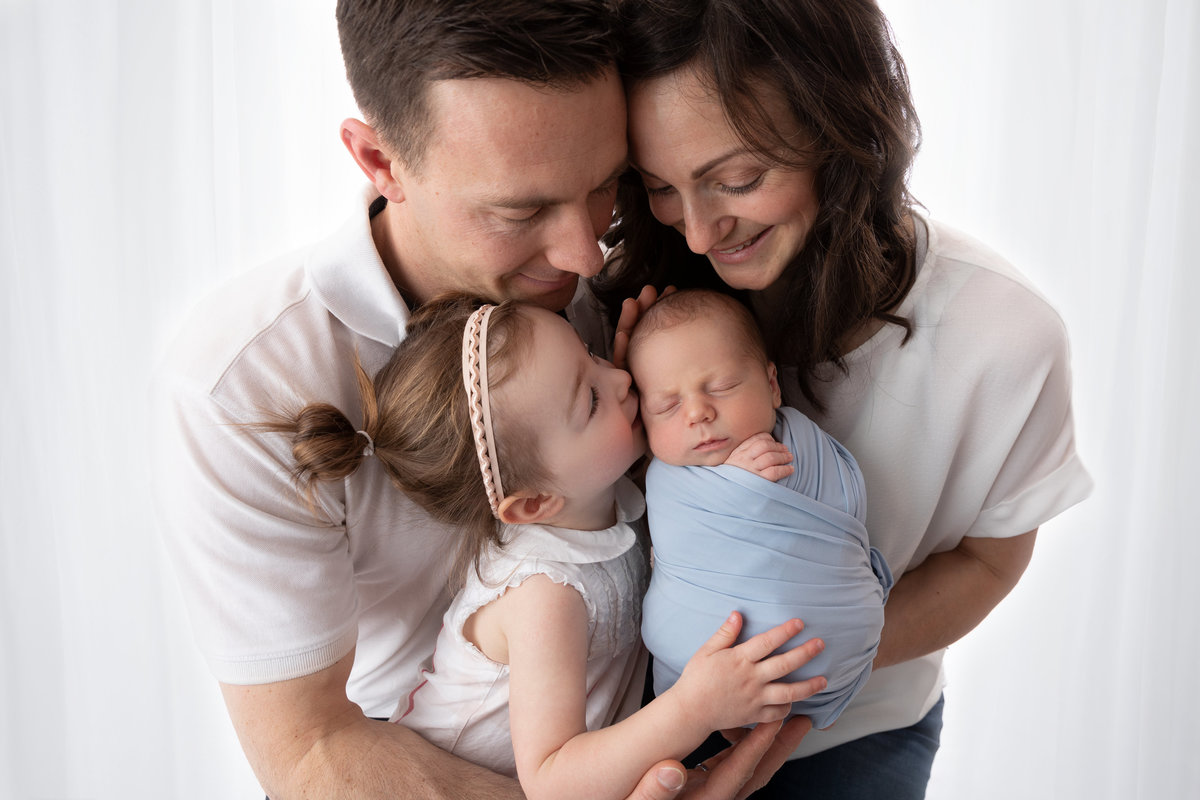 Family with little baby boy & his sister kissing him