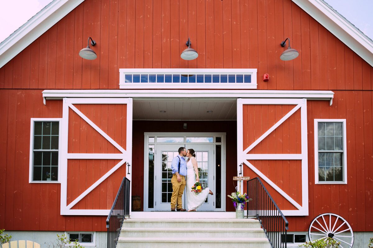 Sterling red barn wedding ceremony with open barn doors