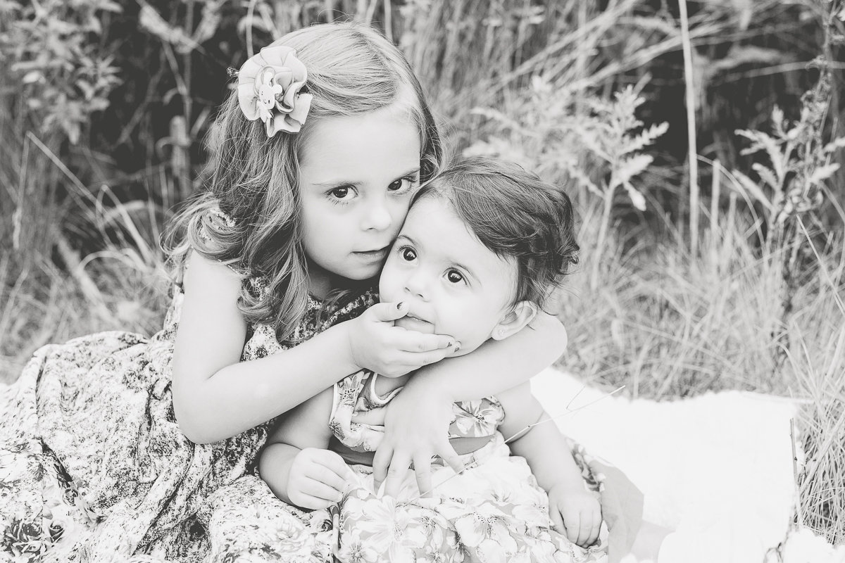 Two sisters hugging outdoors {Mississauga Child Photographer}