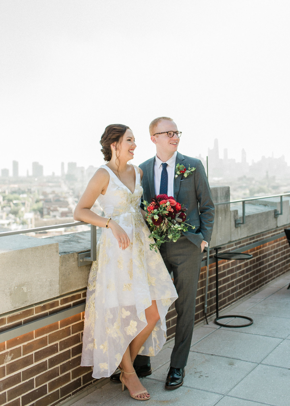 couple smiling on rooftop with skyline in background