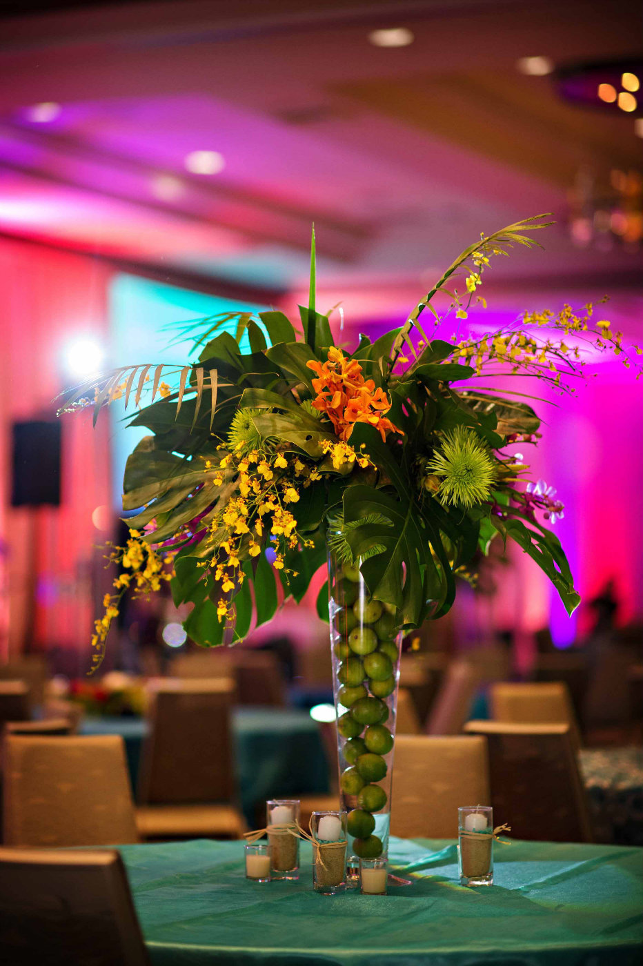 tall centerpiece with tropical leaves, purple orchids, in vase filled with limes on turquoise linen on turquoise linen