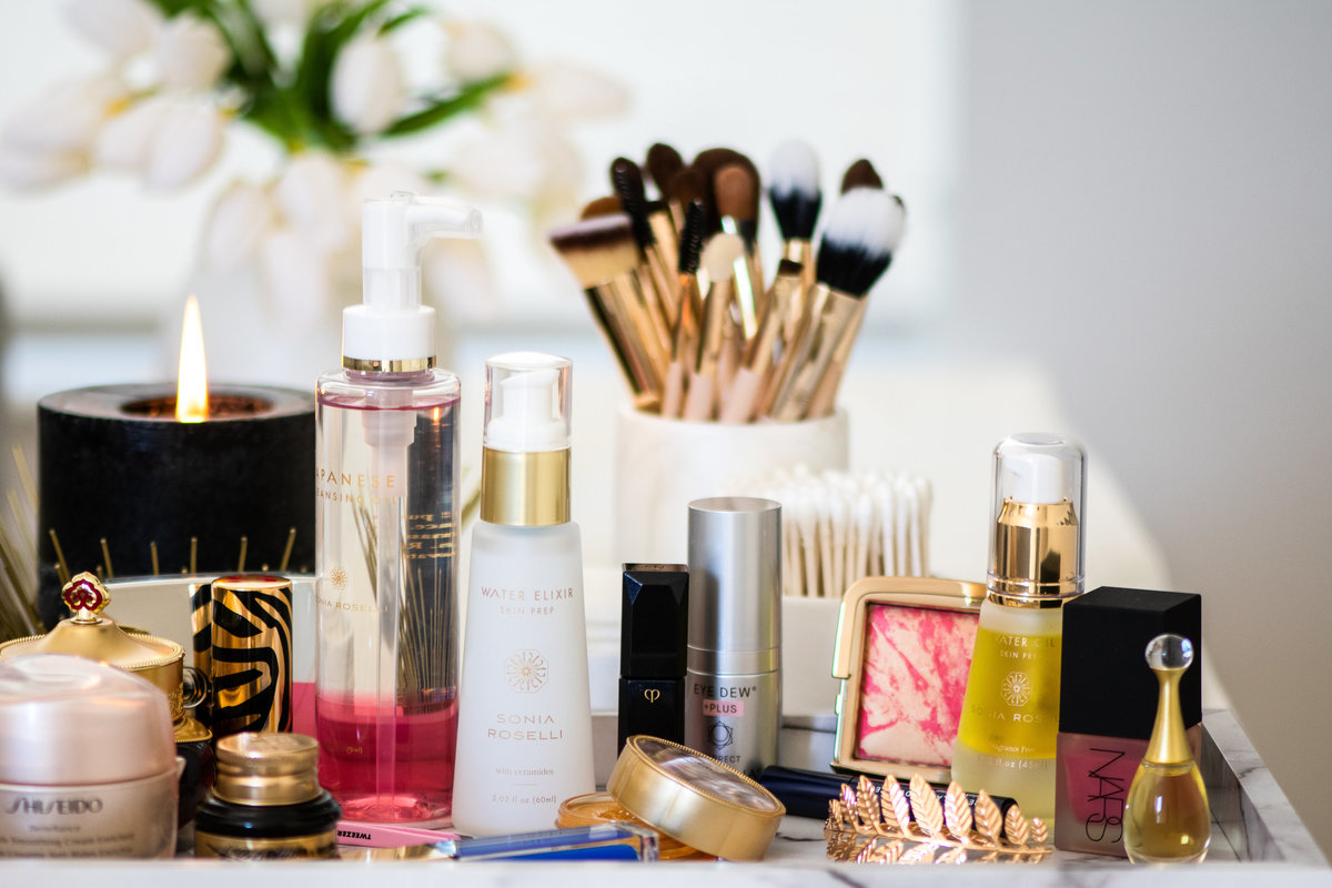 Sonia Roselli Beauty upscale skin prep products sit atop a counter with candle burning and selection of makeup products
