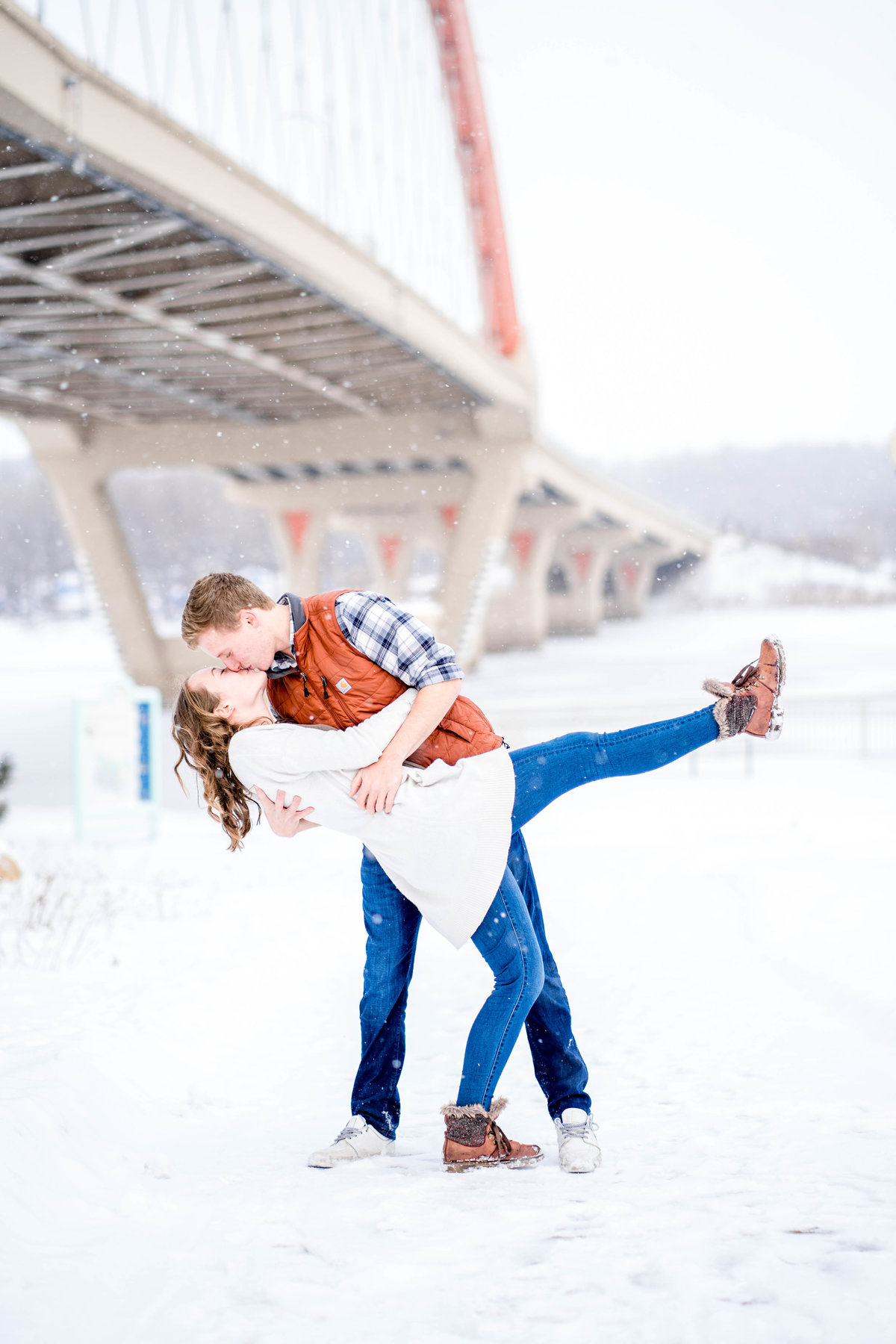 Engagement couple doing a dip in the snow