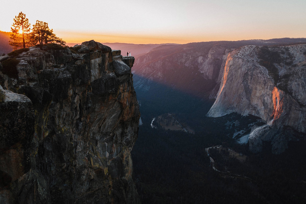 couple on leadge overlooking yosemite valley at sunset