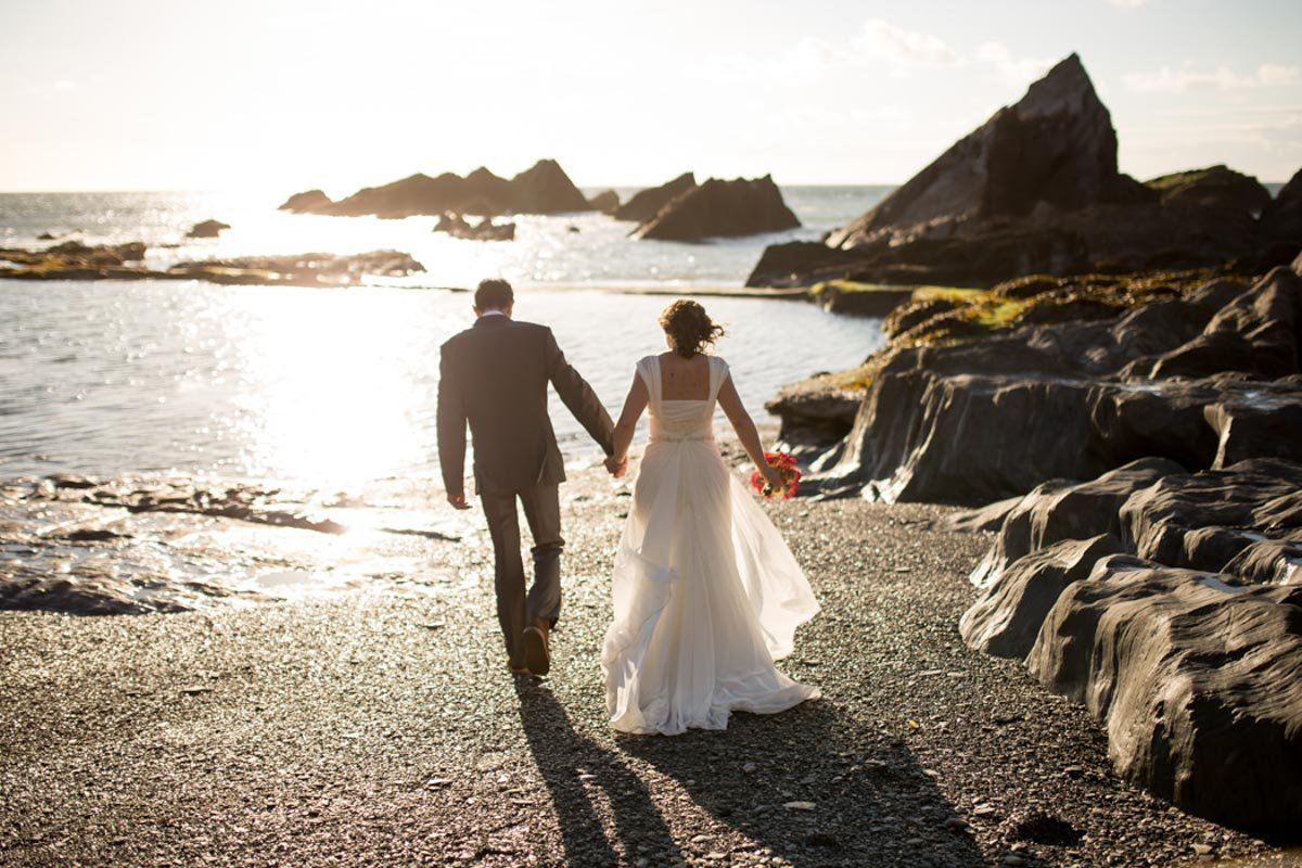 Couple on the beach walking towards the sea at their summer Tunnels Beaches Wedding