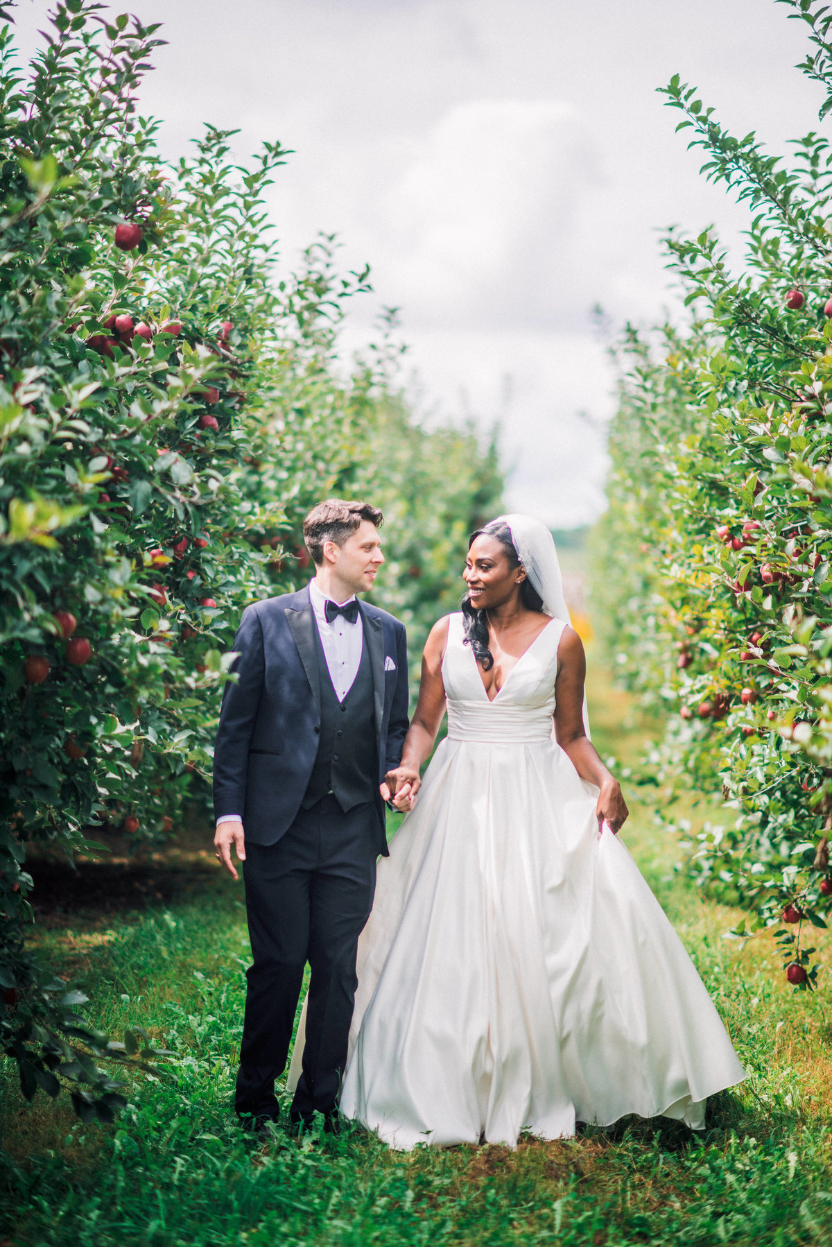 bride and groom walk towards camera in an apple orchard