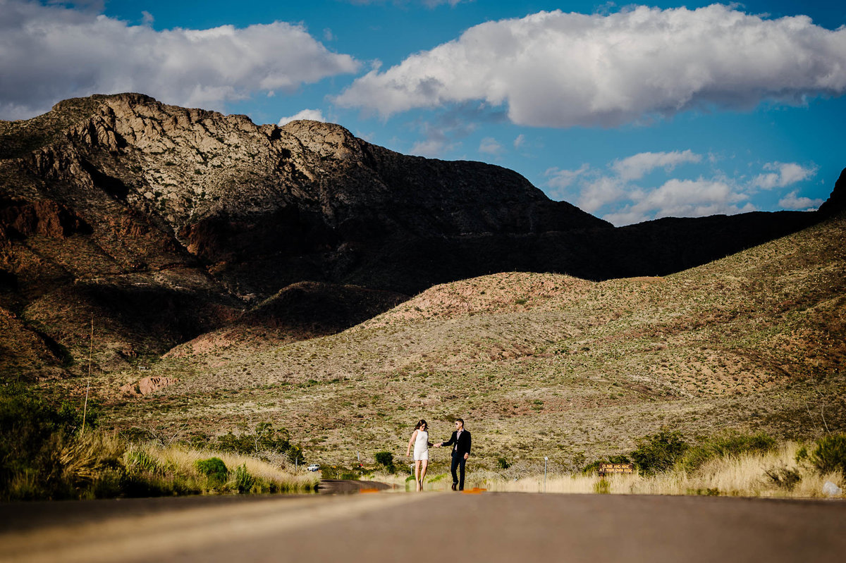 couple walking in front of franklin mountains in el paso