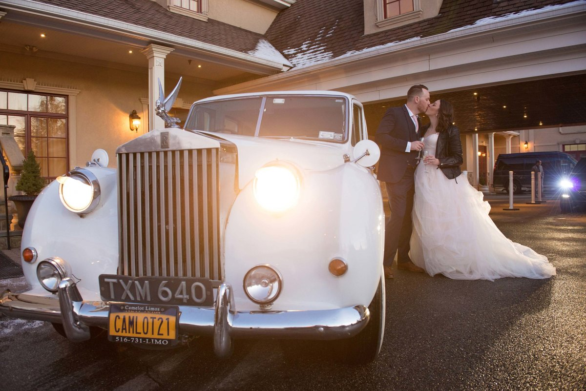 Bride and groom kissing by their vintage car at The Inn at New Hyde Park