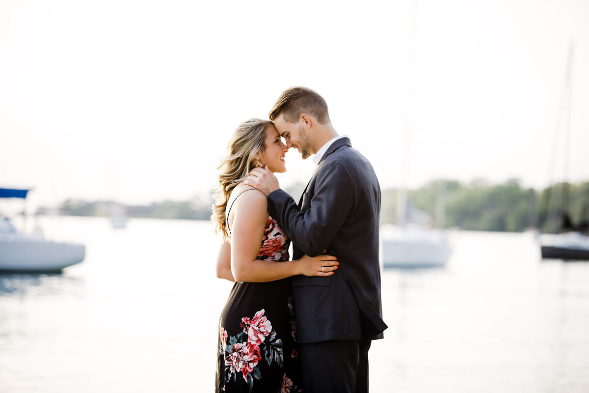 Engaged couple embracing in Buffalo Outer Harbour, New York with harbour boats in background