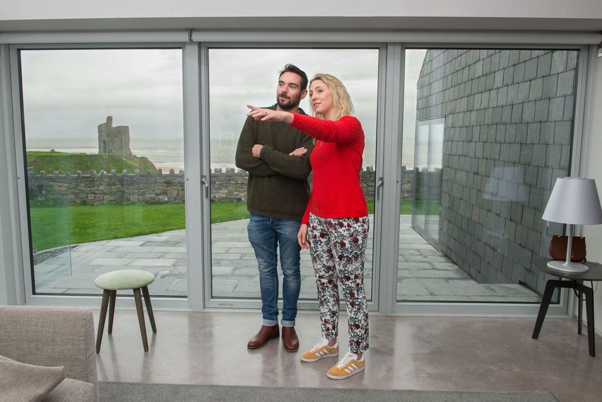 Man and woman standing in a modern house overlooking sea