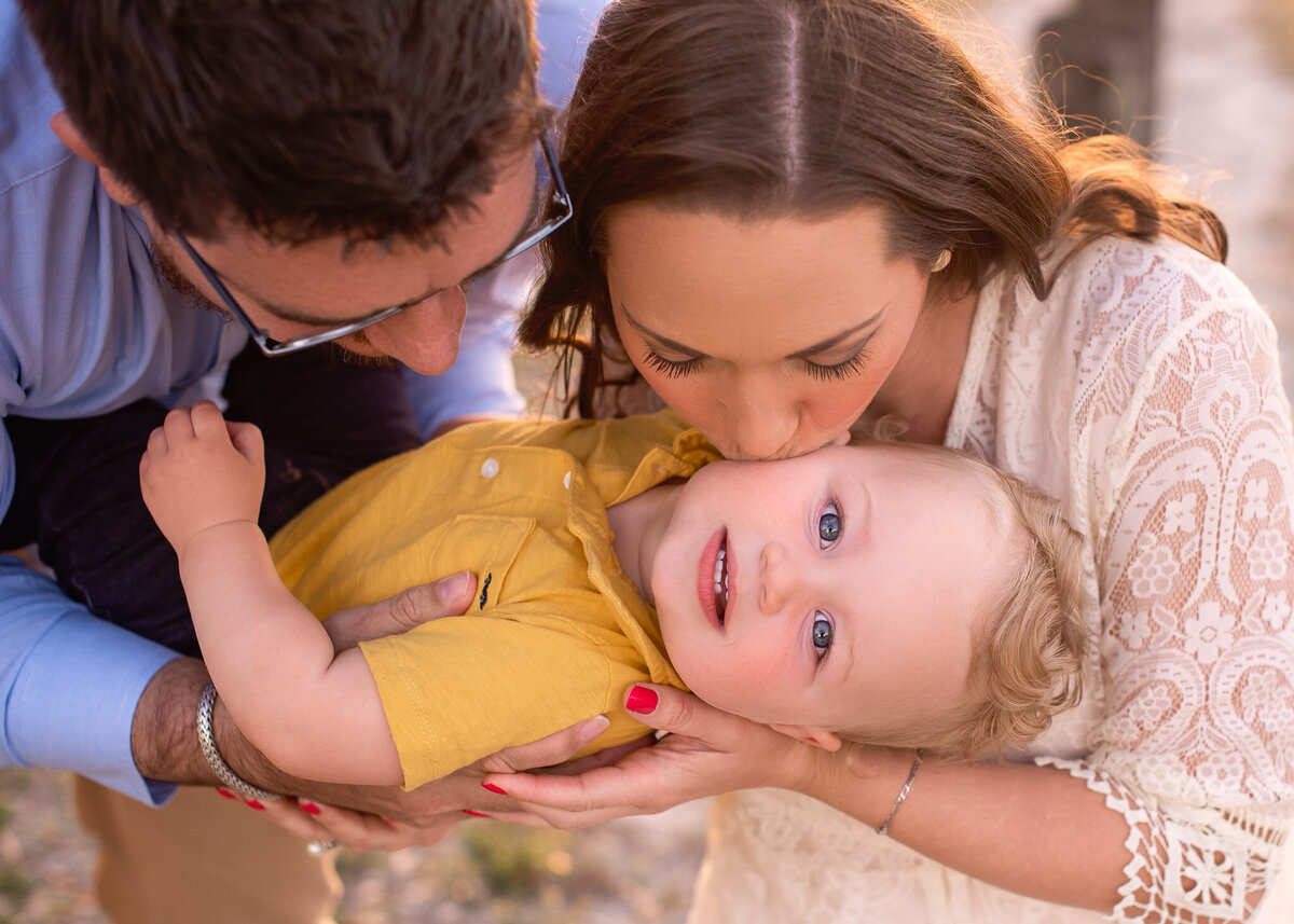 Family of 3 photography session kissing baby