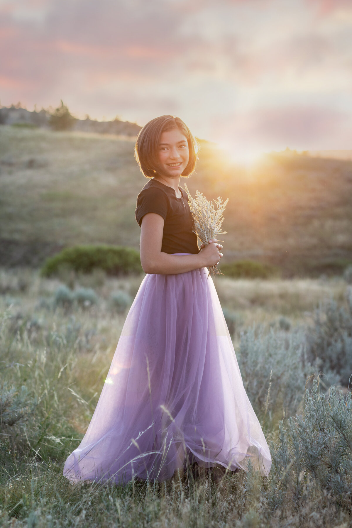 girl in purple and black dress holding sagebrush near sunset at phipps park in billings montana in the summer, sun beam showing through.