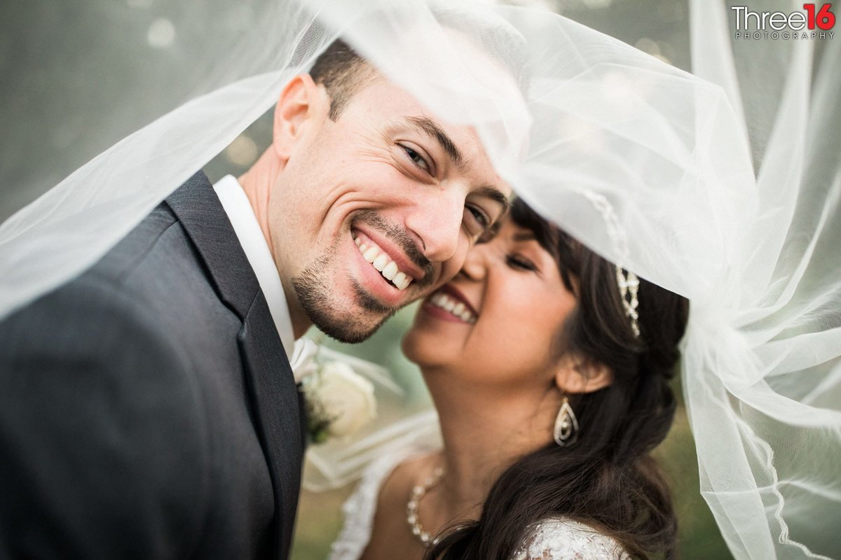 Married couple share a fun moment together under the Bride's veil