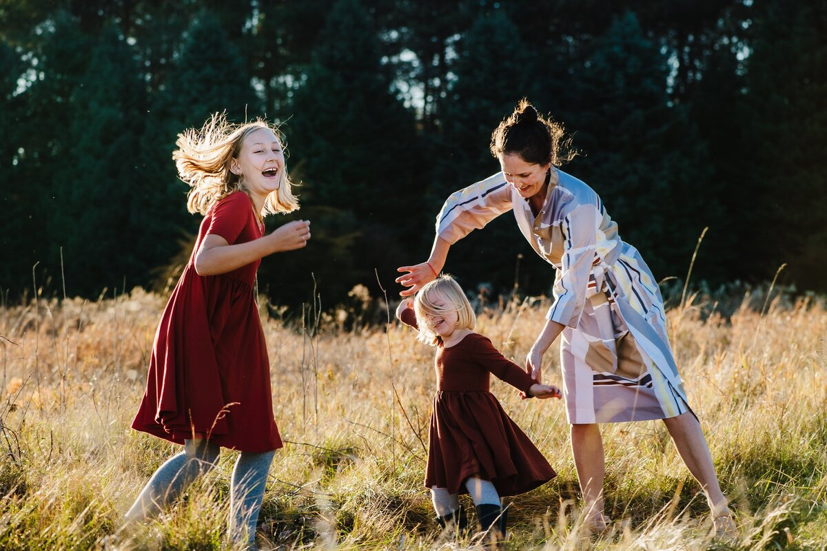 Two children laughing and spinning in field in dresses, mother holding youngest child's hand and dancing with them. Evergreen trees and fall wheat field in front.