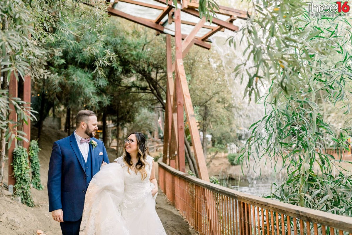 Bride and Groom go for a walk on a dirt path next to a small lake