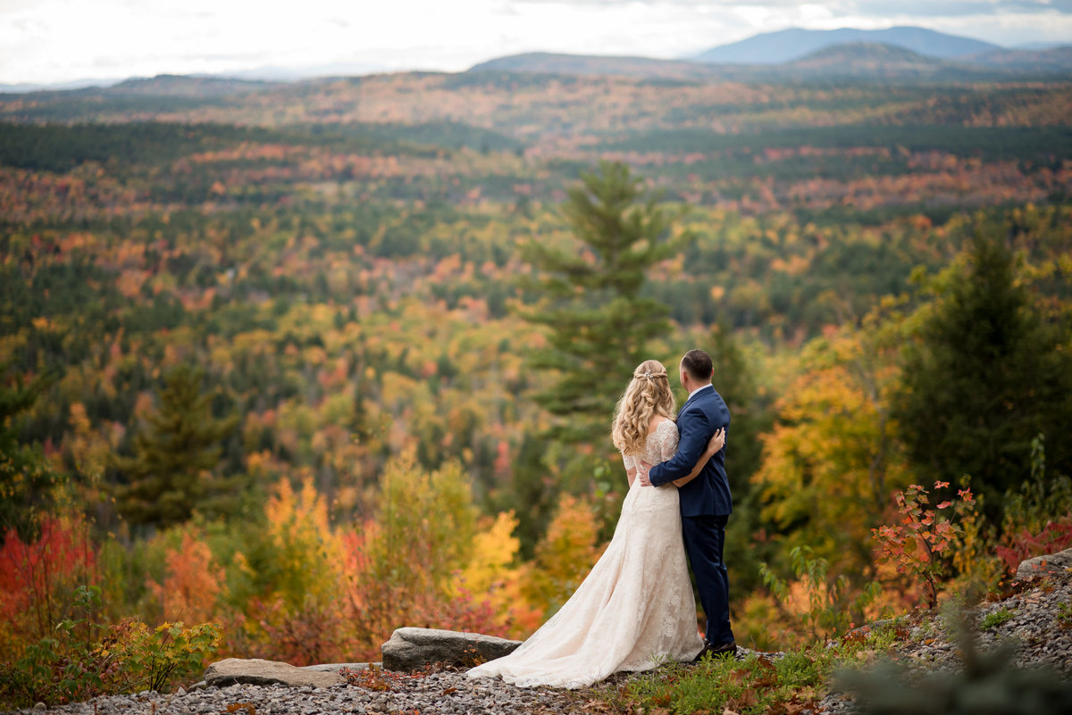 couple posed on a mountain in Maine during fall foliage