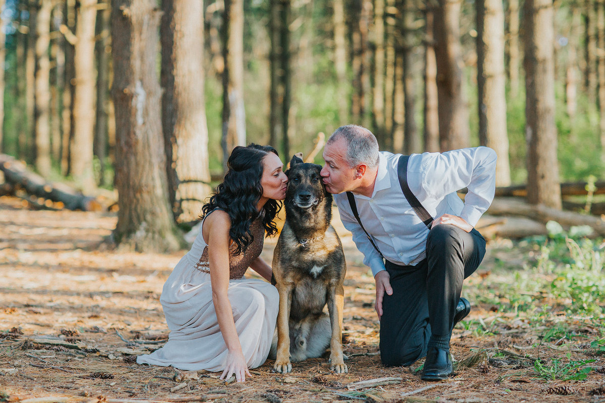 man and woman kissing their dog during their engagement photography session