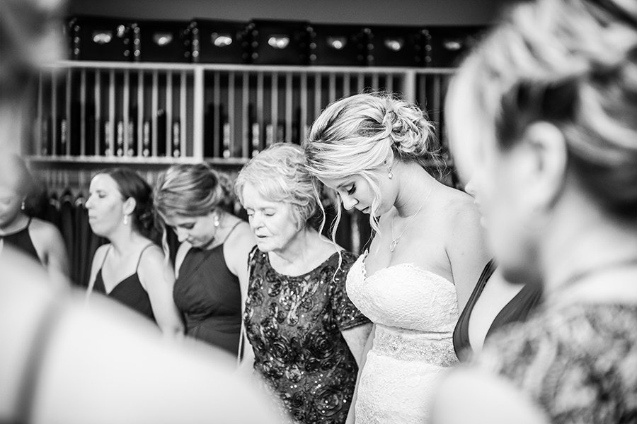 A bride prays with her family and bridal party before the wedding ceremony