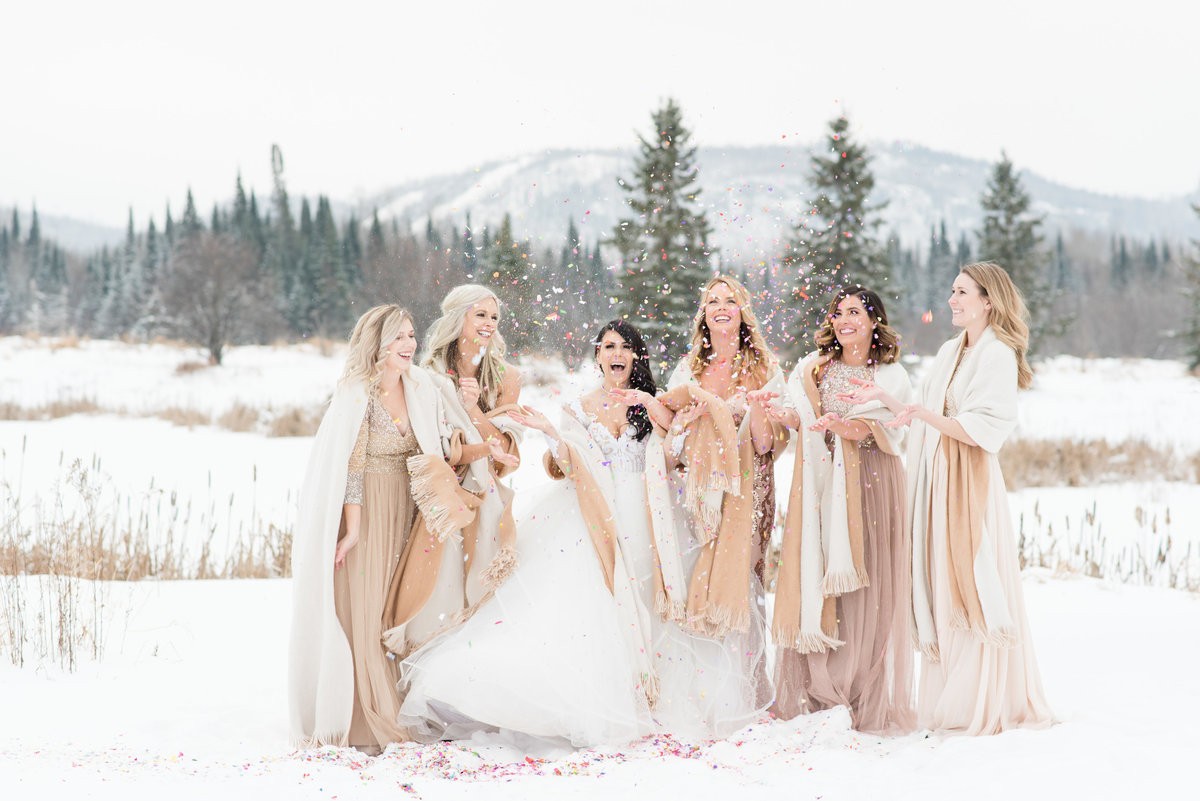 A bride and her bridesmaids stand in the snow and  throw confetti in the air with the beautiful Norwester mountains in the background