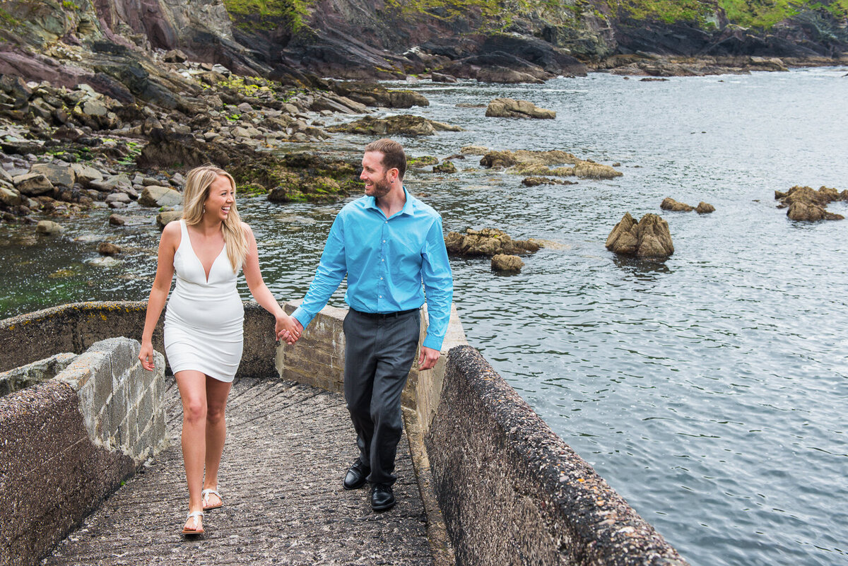 Engagement photograph of a man and woman  holding hands and walking on a pier