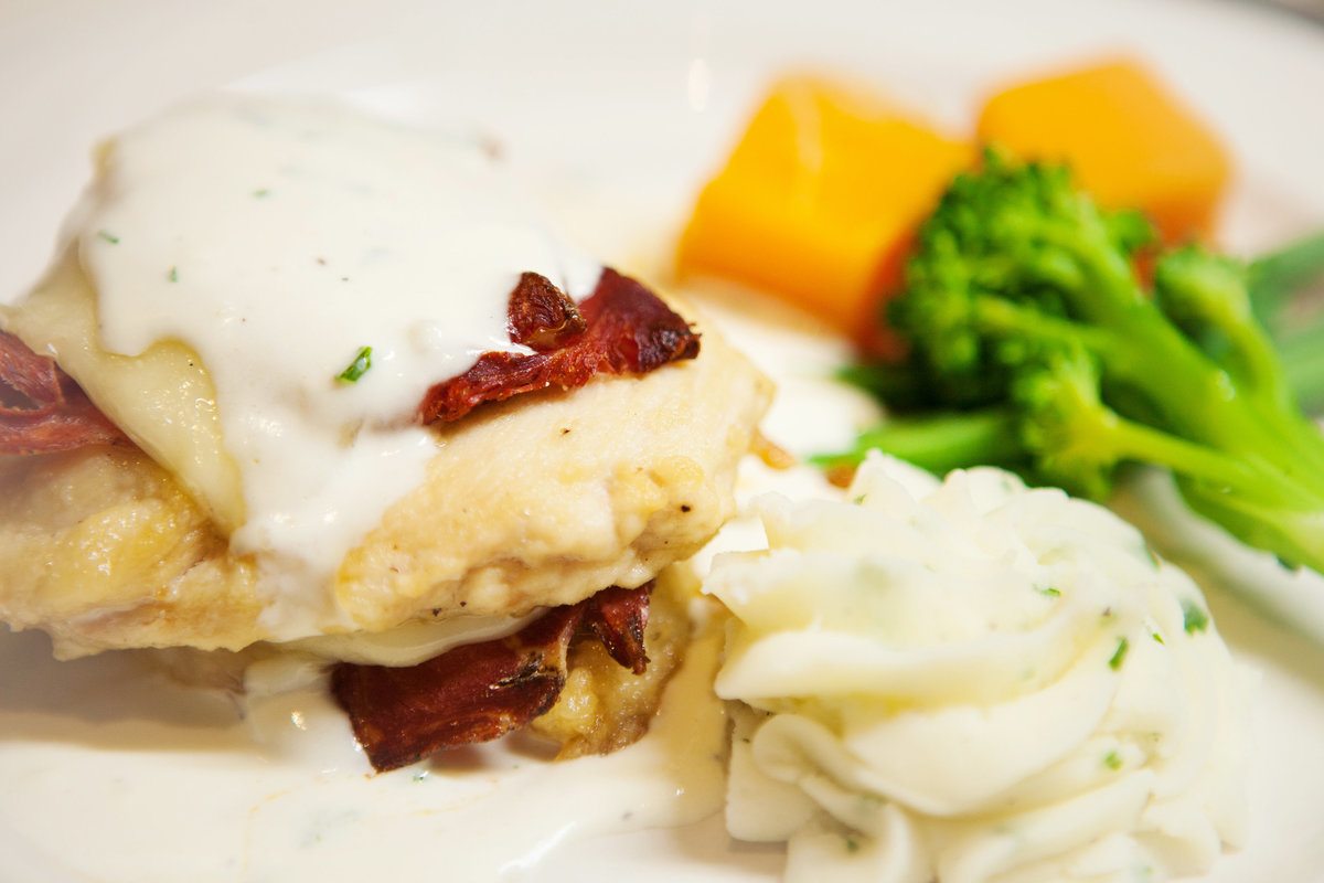 Chicken Cordon Bleu grilled chicken breast layered with provolone, dry-cured ham & topped with a garlic-crème sauce