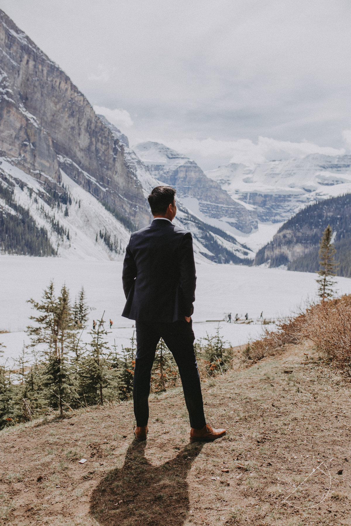 Groom overlooking Lake Louise after ceremony at Lake Louise by Lake Louise Photographer Lindsay Copeland of Twenty Twenty Photography