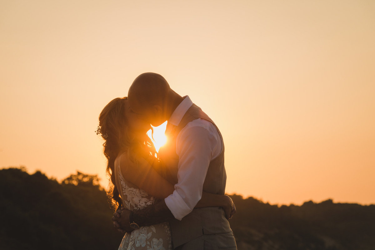 photo of bride and groom kissing during beach sunset wedding at Pavilion at Sunken Meadow