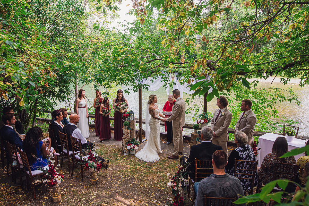 Bride and groom hold hands during their intimate garden wedding ceremony