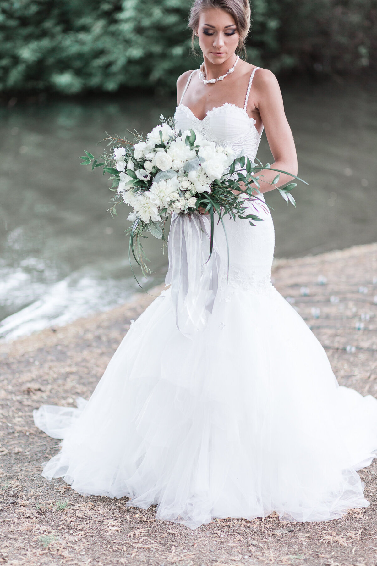 Kaloya Park Okanagan Bride by the water in couture gown with floral bouquet