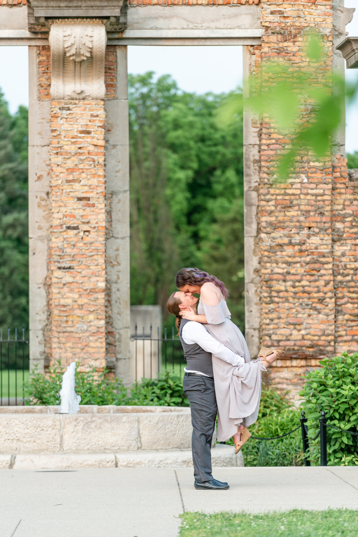 Man with ponytail lifts bride wearing soft grey dress in front of the ruins at Holliday Park in Indianapolis