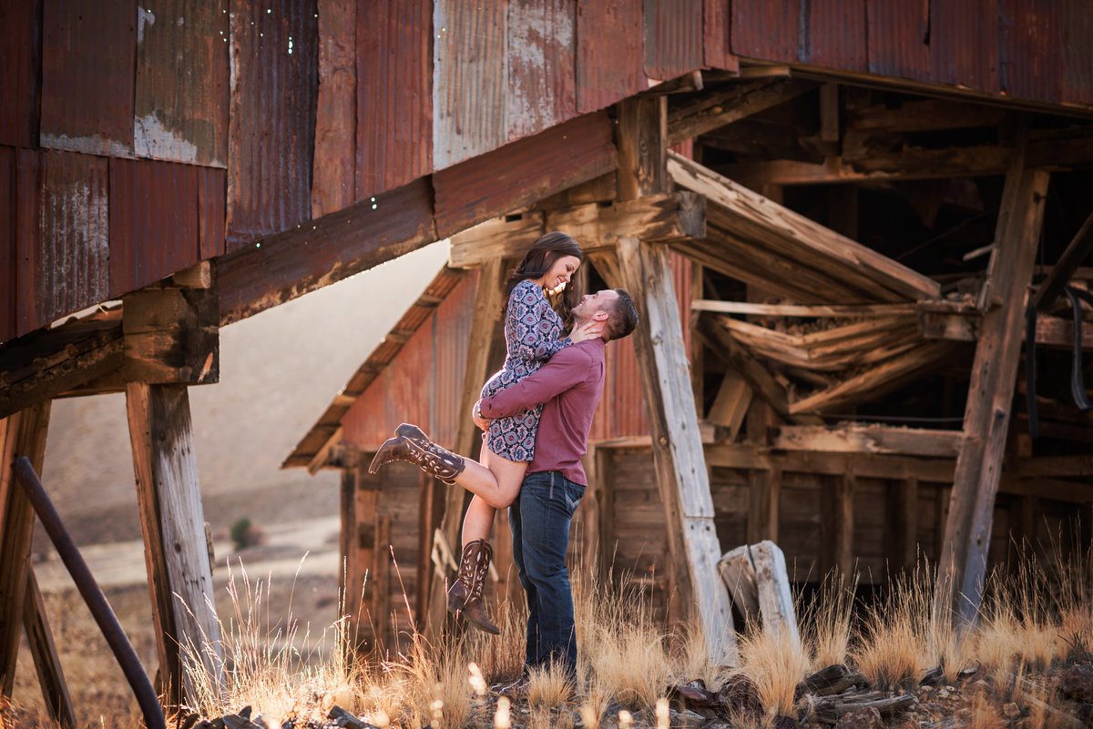 Man lifts and spins woman in rustic setting