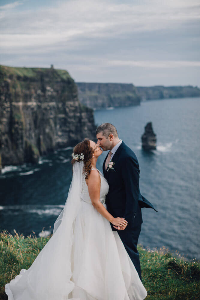 Ireland & US Wedding Coordinator, bride and groom kissing on cliffside