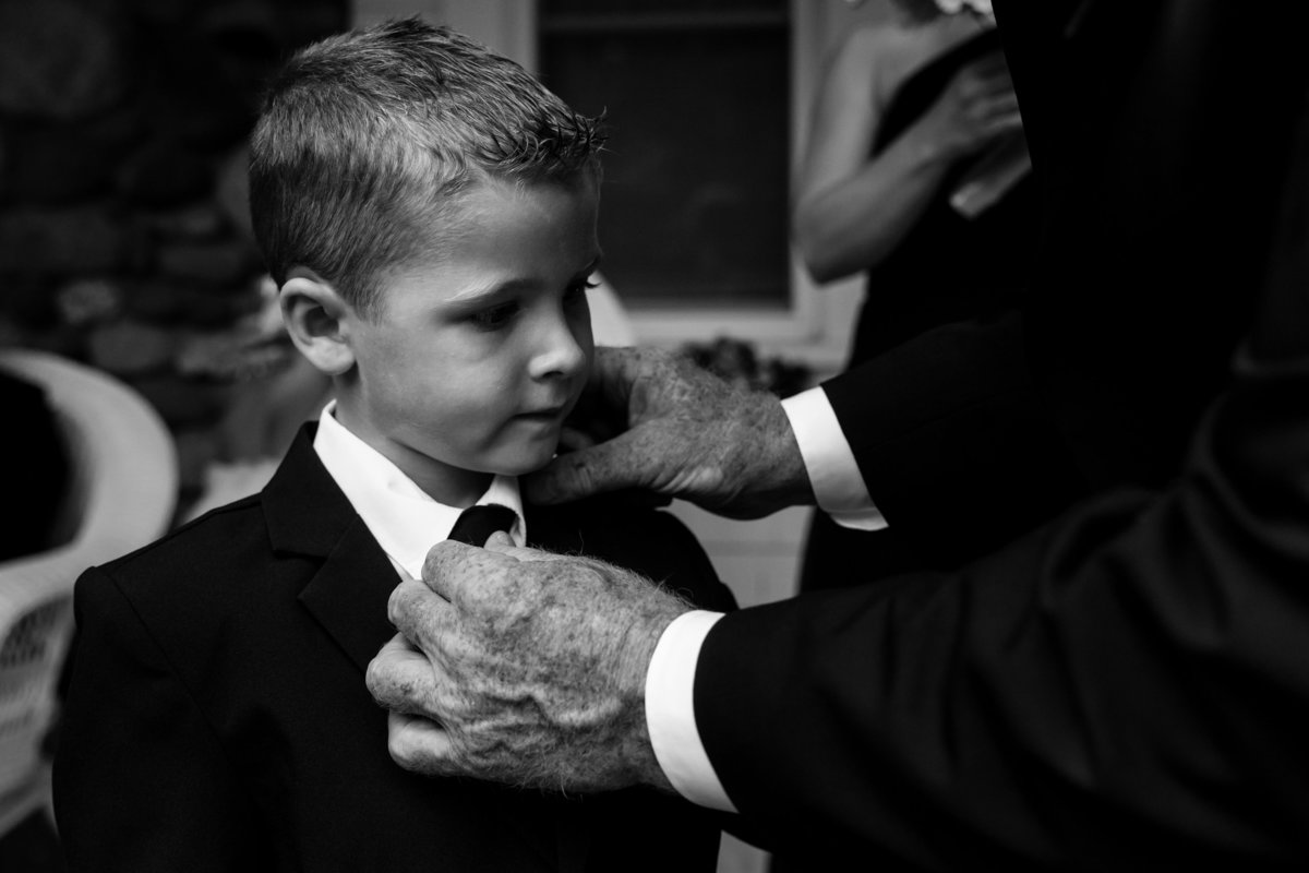 The father of the bride adjusts his grandson's tie at the Pot & Kettle Club wedding  in Hulls Cove Maine