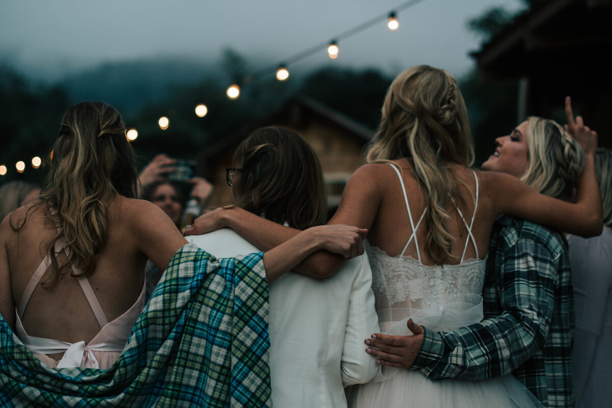 Bride-with-three-friends-from-behind-dancing-at-wedding-ceremony-laughing