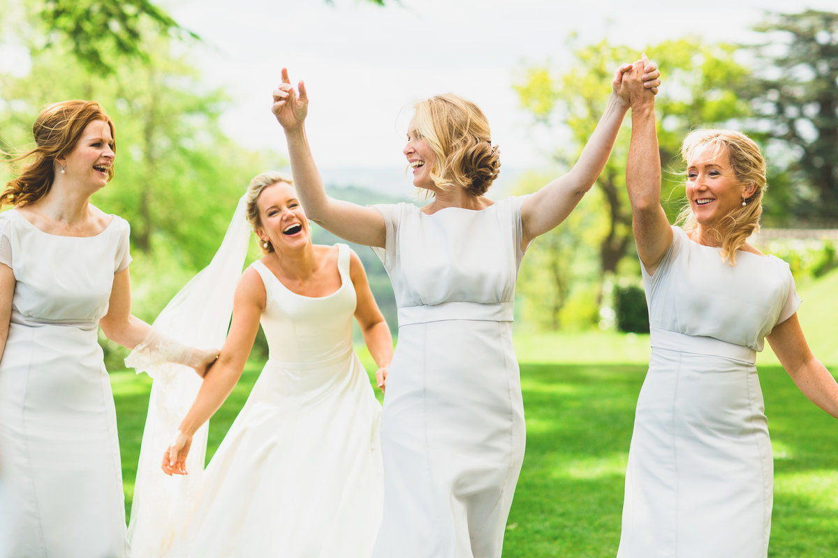 bridesmaids holding hands and laughing at hedsor house hertfordshire