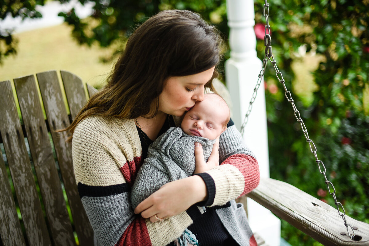 Beautiful Mississippi newborn photography: Mom kisses newborn boy on farmhouse porch swing in Mississippi