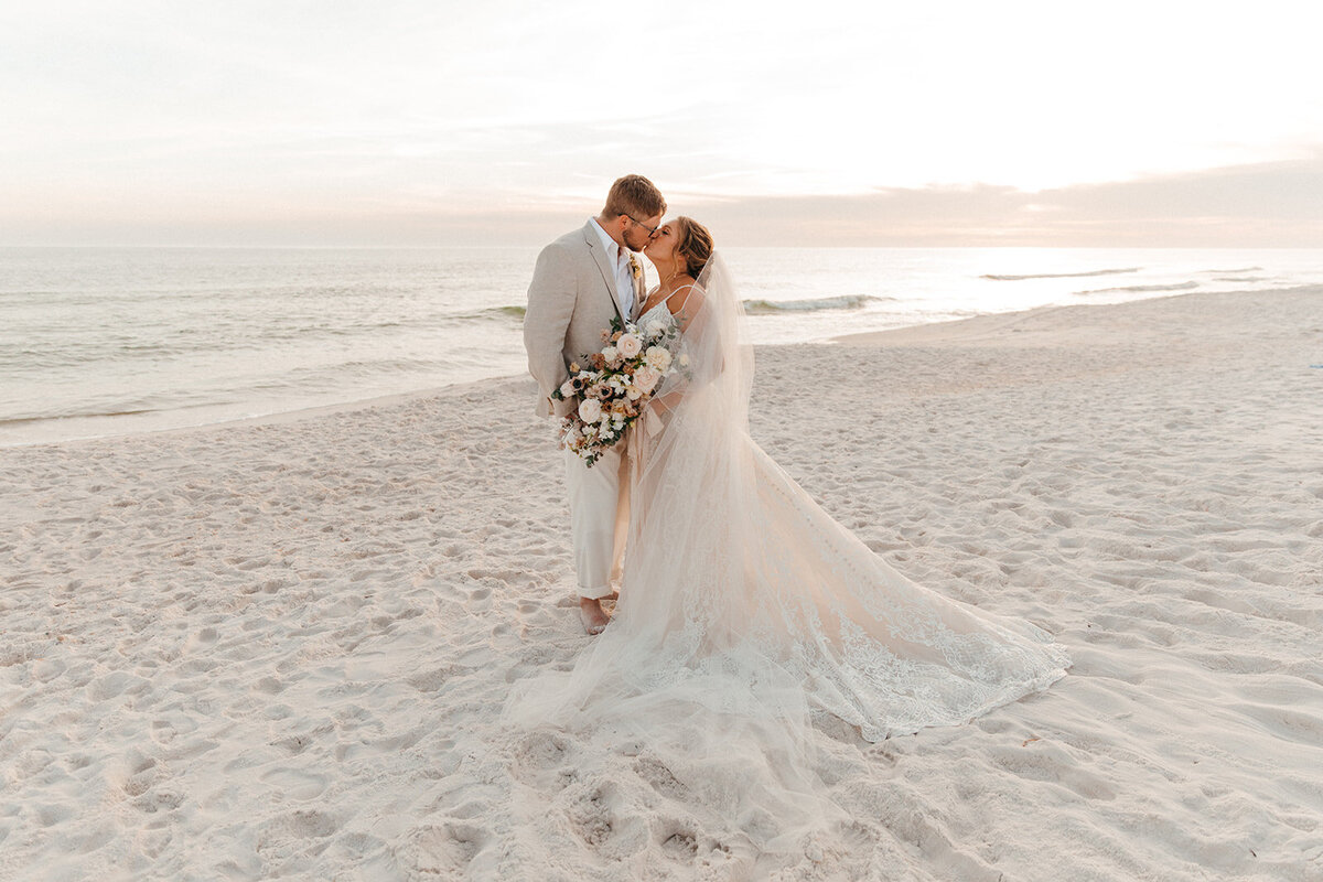 Bride and groom kiss on a 30a beach