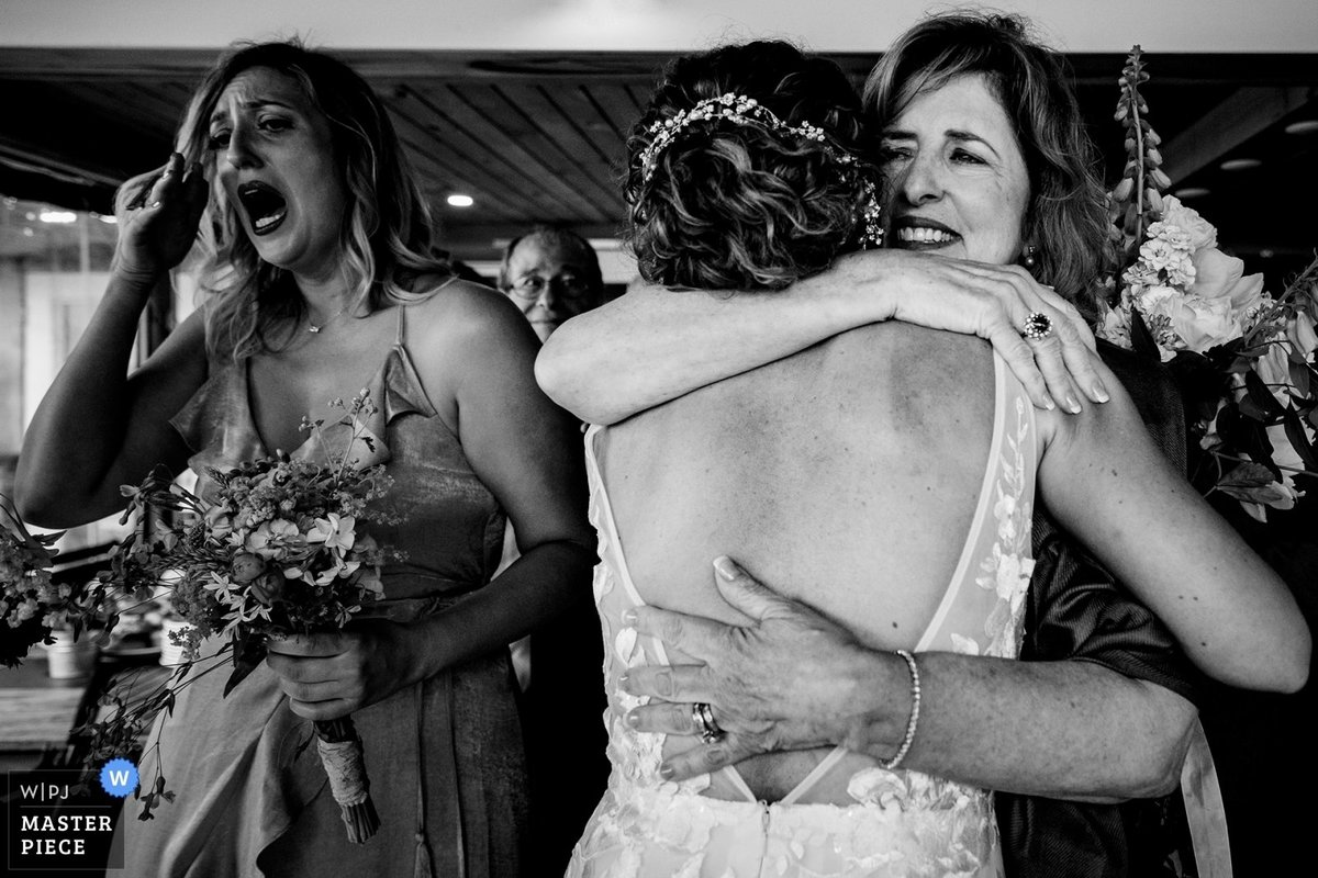 Linekin Bay Resort Wedding the bride hugs her mother in law as a tearful bridesmaid stands next to them at the Maine camp ceremony