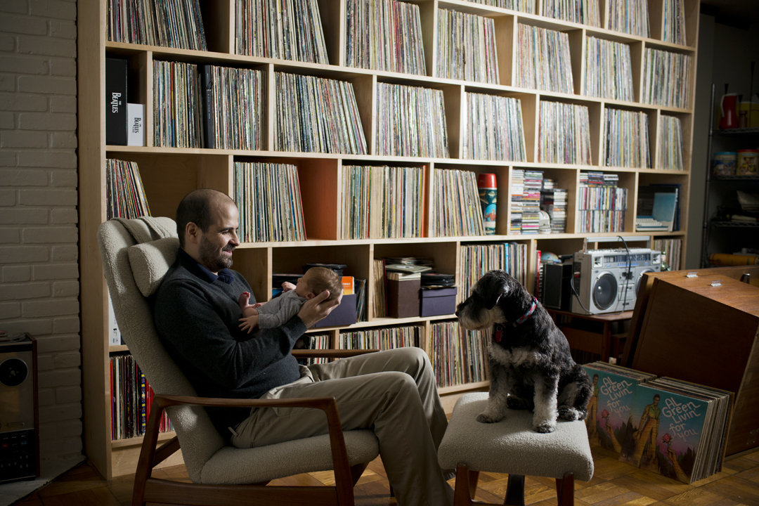 Father with record collection, holding newborn son.