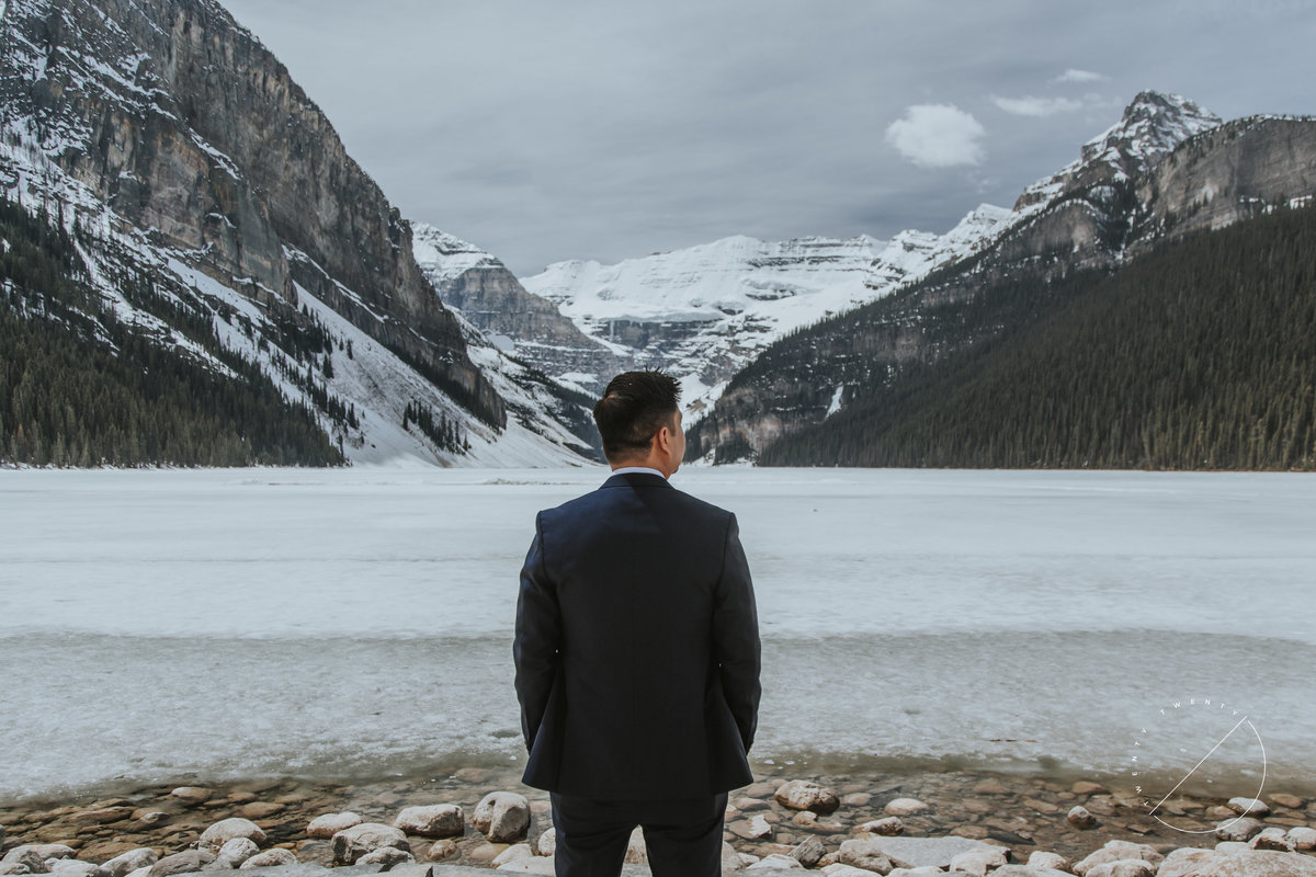Groom overlooking Lake Louise during winter wedding captured by Twenty Twenty Photography
