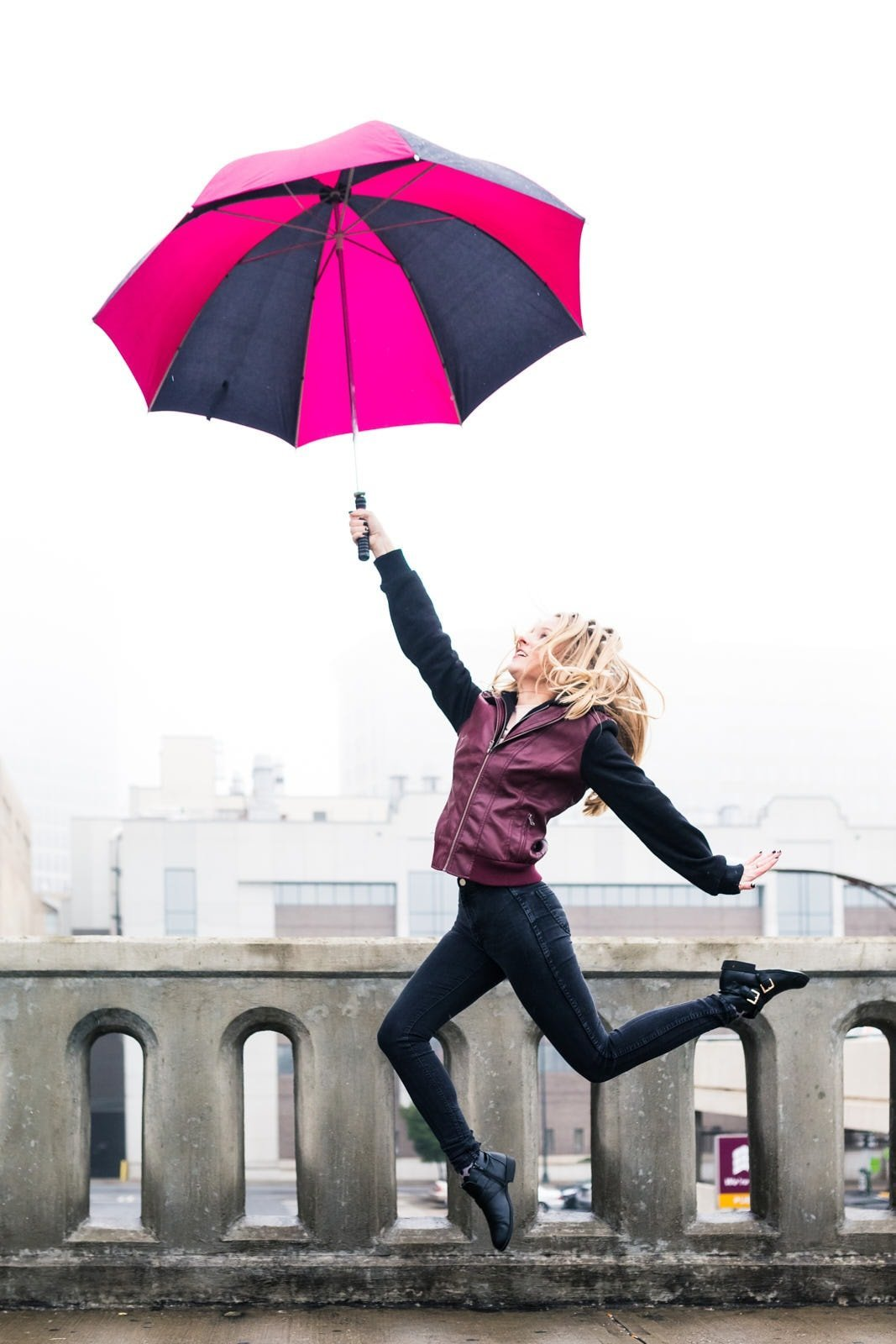 girl leaps with pink umbrella in rain on downtown Atlanta bridge