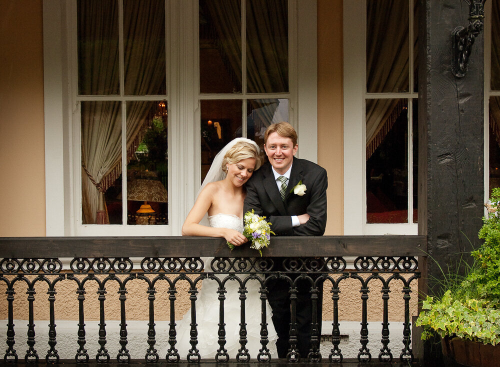 Bride with blonde hair, wearing a princess style wedding dress, holding a white flower bouquet, relaxing with her groom on the veranda of the Muckross Park Hotel
