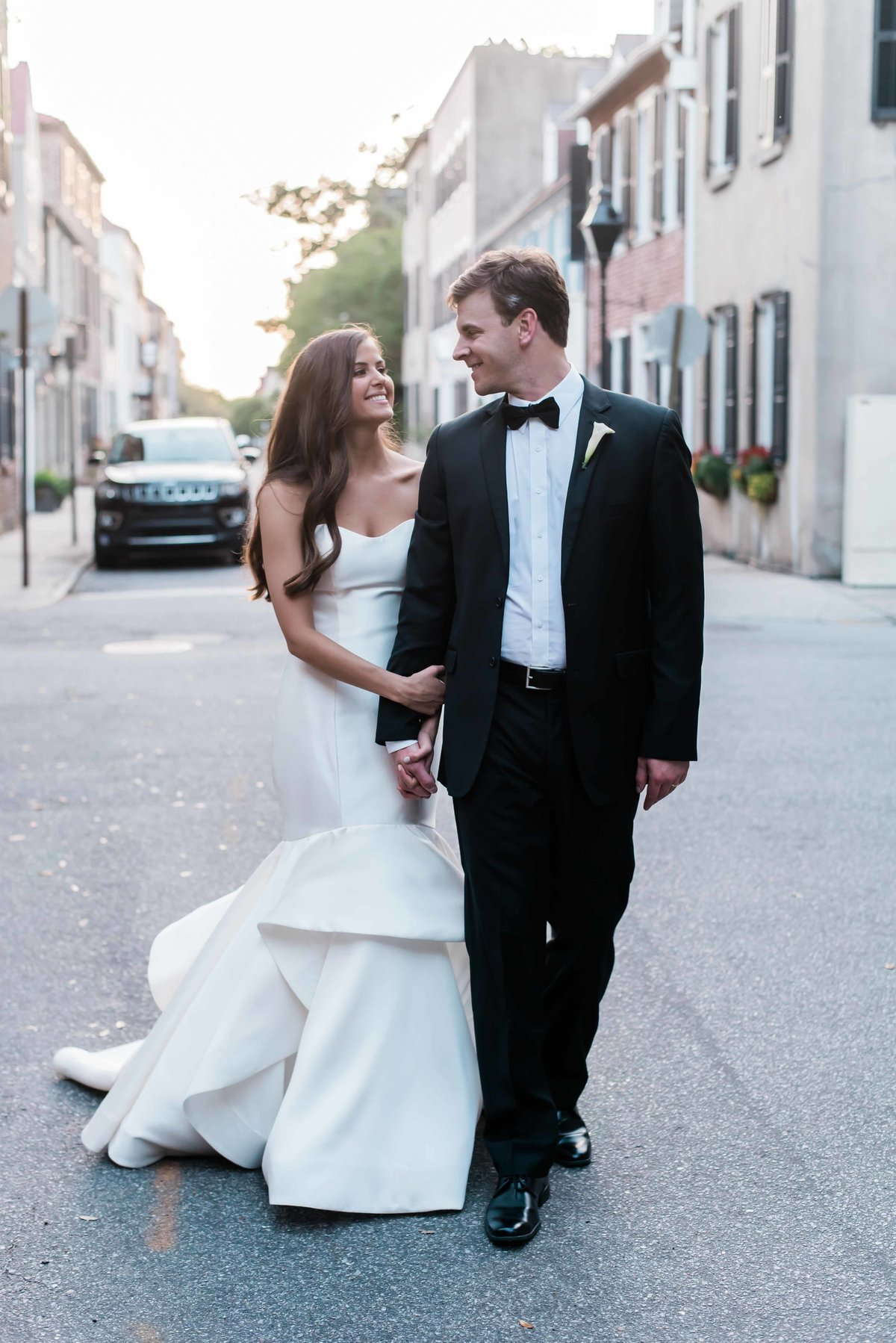 Bride and groom take a stroll through downtoan Charleston, SC at sunset