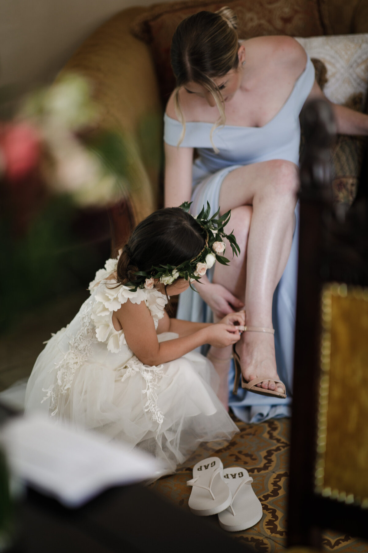 Flower girl assists bridesmaid with her shoes