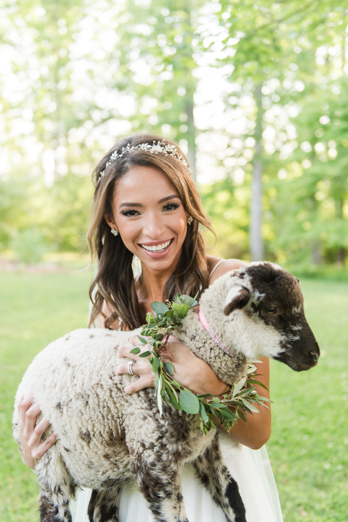 Bride with baby lamb at estate wedding