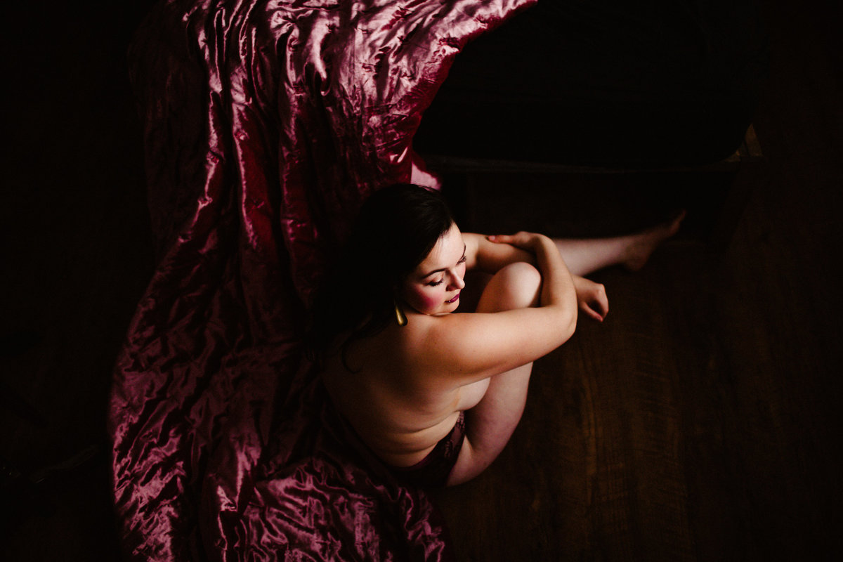 woman with knee up sitting on pink velvet bedspread