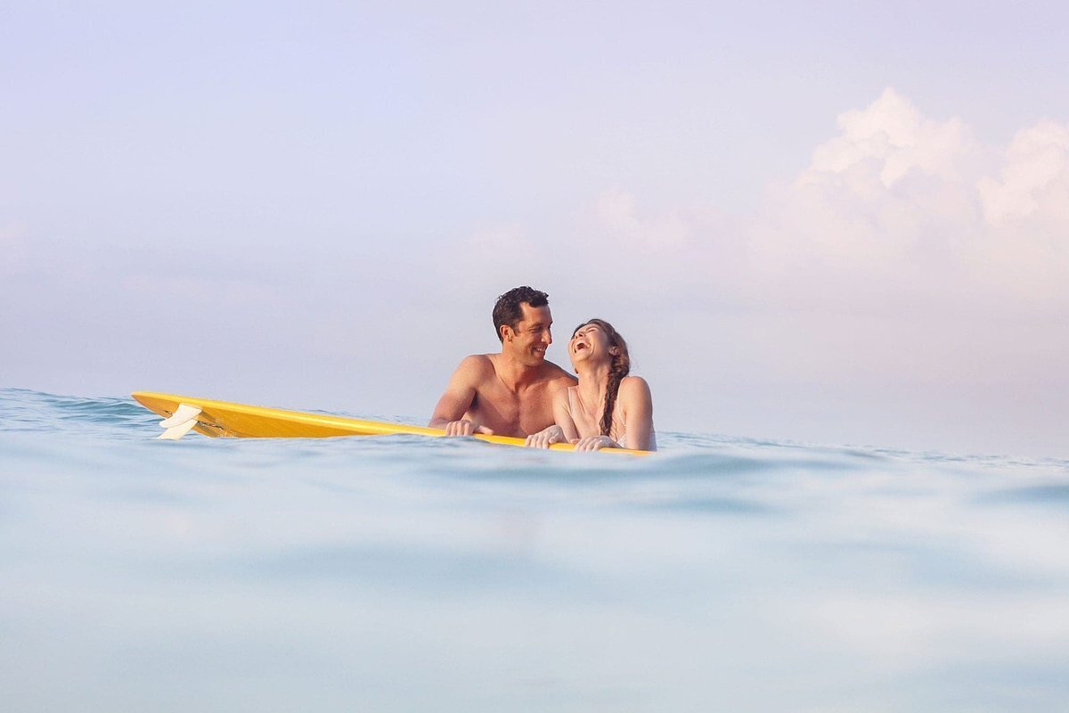 Couple in the ocean on Maui smiling with surfboard