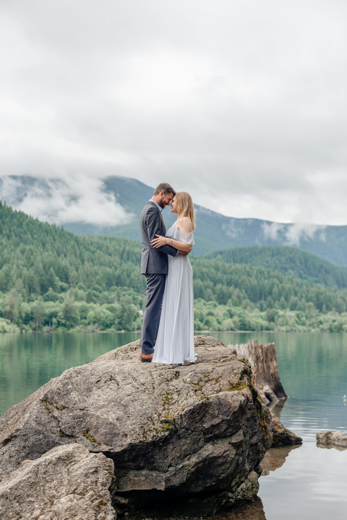 Couple stands on large boulder in Rattlesnake Lake just outside of Seattle